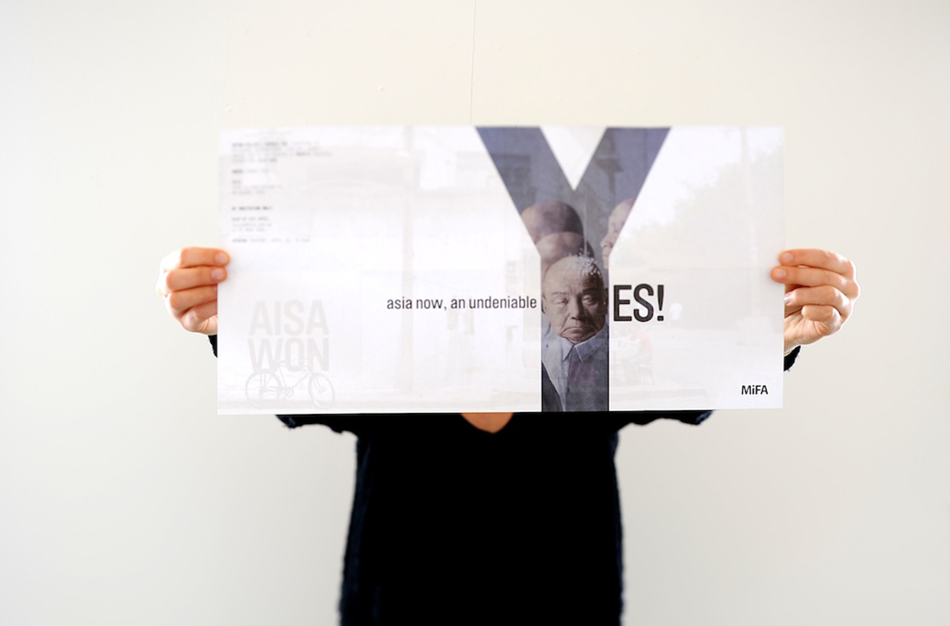 person holding poster for mifa art show advertising