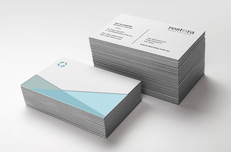 restora health logo embossed on business card stack