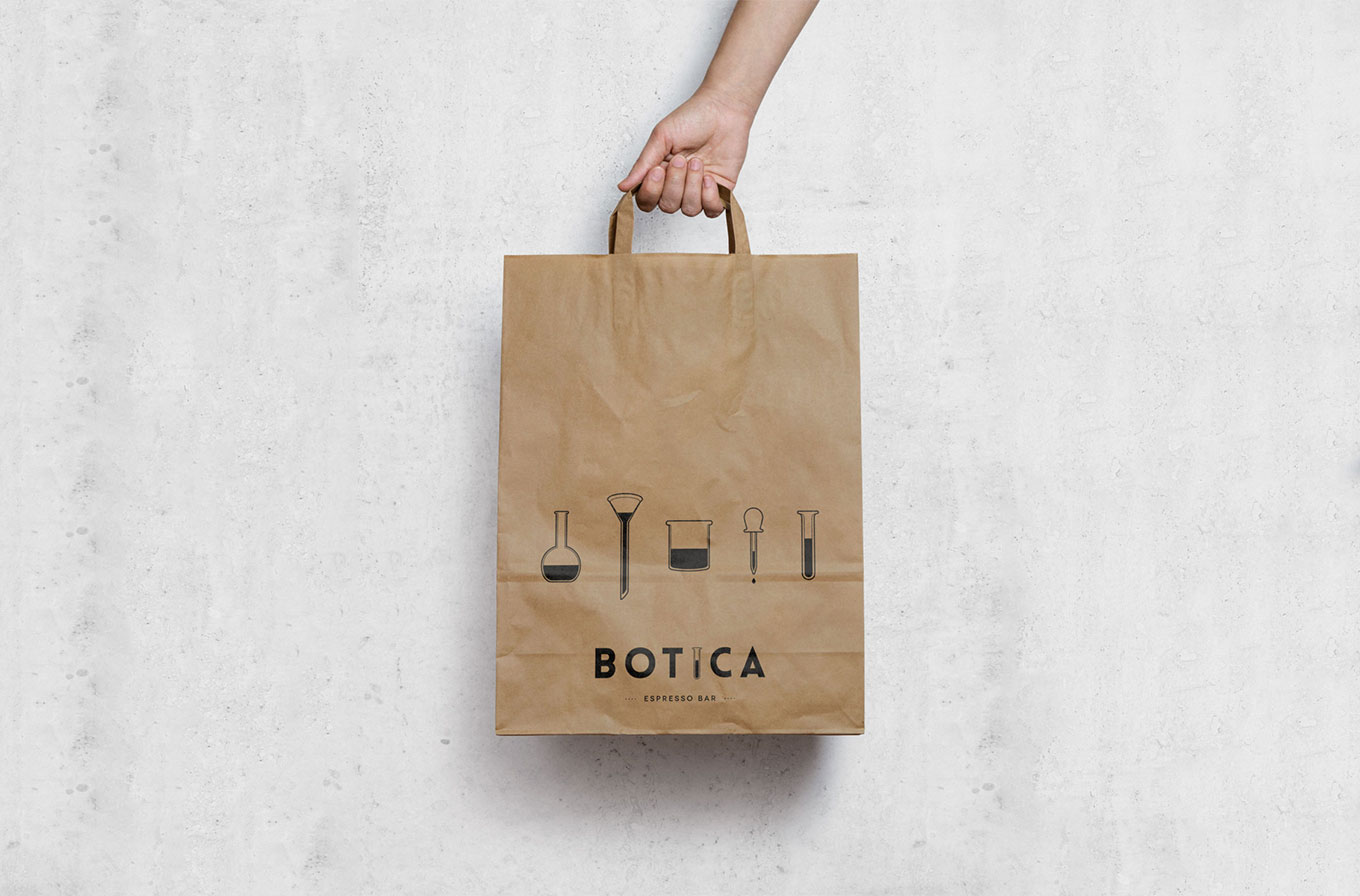 hand holding botica cafe branded paper bag