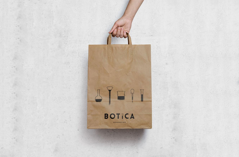 hand holding botica cafe branded paper bag