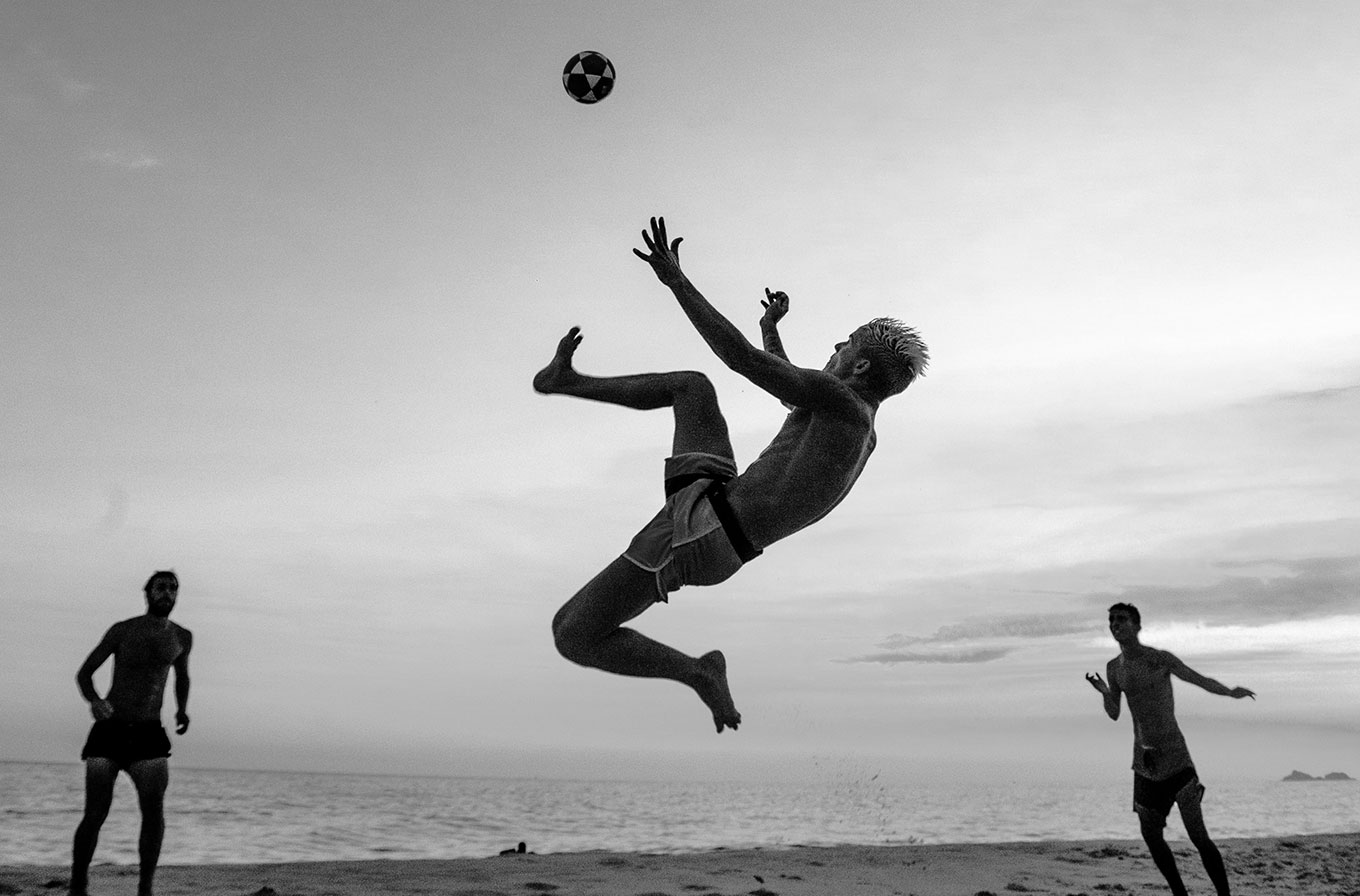 boy jumping in the air an kicking football beach